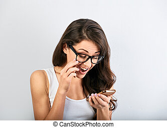 Excited beautiful woman in eye glassses with opened mouth reading text and looking on mobile phone in the hand on blue background