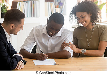 Excited black couple sign agreement at realtor office