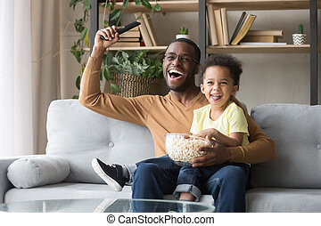 Excited black father with toddler son watching sport tv game