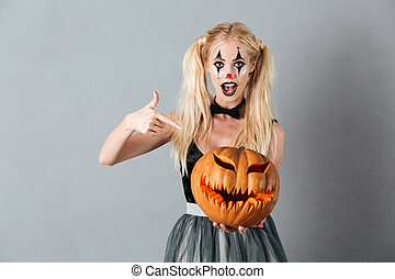 Excited blonde woman in halloween clown make-up