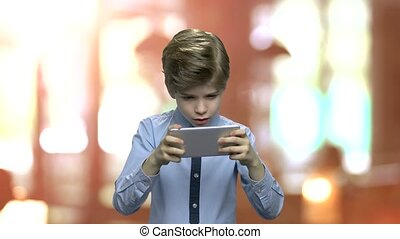 Excited boy playing game on his phone.