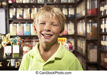 Excited Boy Standing In Sweet Shop