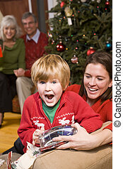 Excited boy with family and presents at Christmas - Happy...