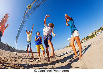 Excited boys and girls playing beach volleyball