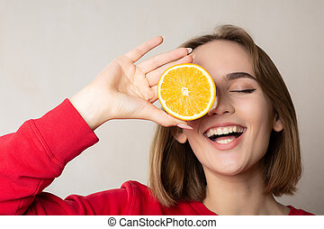 Excited brunette model posing with a half orange, covering one eye, against white wall. Empty space
