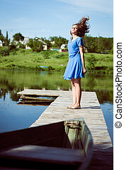 Excited brunette young girl flying her long hair on bridge