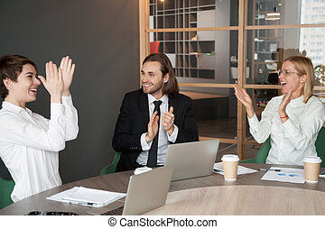 Excited business team applauding congratulating partner with suc