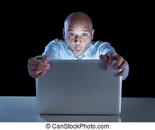 businessman alone at night sitting at computer laptop...