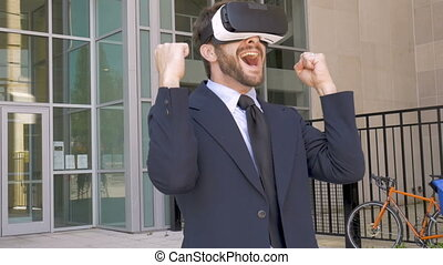 Excited businessman in augmented virtual reality with VR goggles in slow mo