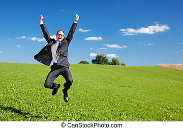 Excited businessman jumps high in the air cheering and...