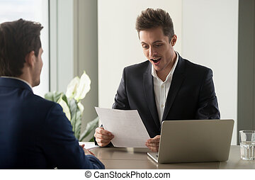 Excited businessman looking amazed while reading document, impre