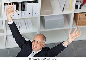 Excited Businessman With Arms Raised In Office