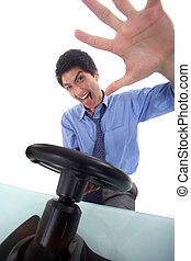 Excited businessman with video game steering wheel