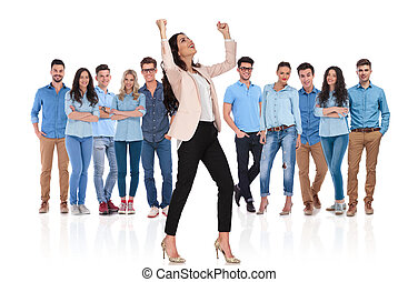 excited businesswoman celebrating while standing in front of her team
