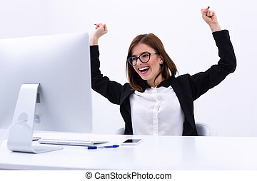 Excited businesswoman rejoicing at her success cheering and raising her fists in the air