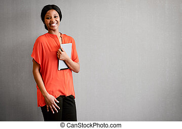 excited businesswoman smiling at camera while holding a digital tablet