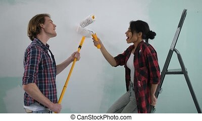 Excited carefree couple having fun painting wall