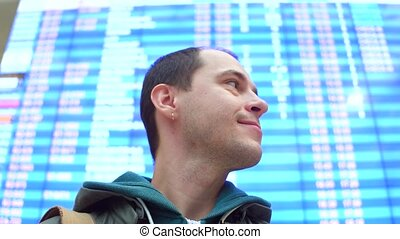 Excited caucasian man looking around near airport departure board. Tourism, travel, waiting concepts. 4K low angle steadicam video