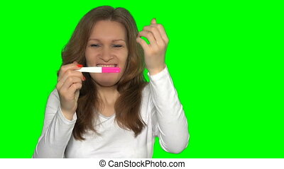 excited caucasian woman looking at pregnancy test. Green...