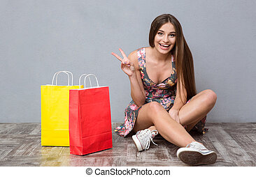 Excited cheerful young woman sitting on floor showing peace sign