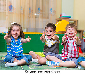 Excited children holding thumbs up - Group of excited...