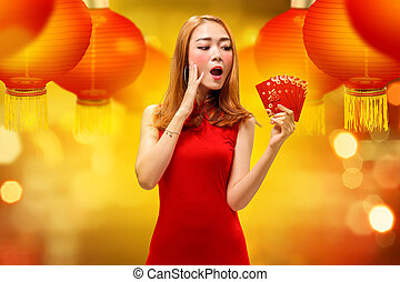 Excited chinese woman in traditional dress holding angpao
