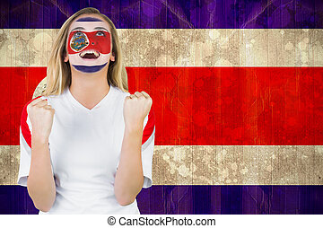 Excited costa rica fan in face paint cheering against costa...