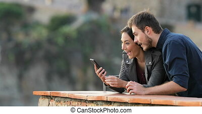 Excited couple checking phone content in a balcony - Excited...