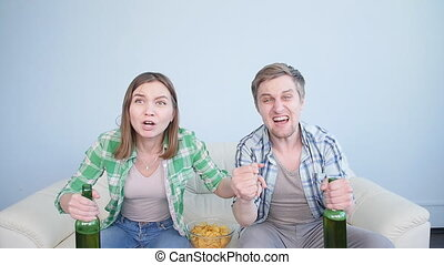 Excited couple sports fan watching tv on a sofa in the living room