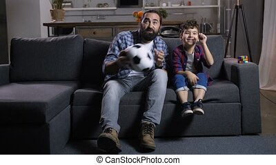 Excited bearded father and joyful adorable son sitting on sofa with soccer ball toy, watching football match on television, cheering their team, expressing positivity while enjoying game at home.