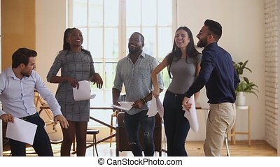 Excited successful diverse business team having fun throwing tossing papers celebrate corporate success victory win, happy overjoyed motivated multiracial colleagues group dancing laughing in office