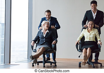Excited diverse employees laughing riding on chairs in office