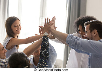 Excited diverse office team giving high five together celebratin