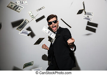 Excited emotional businessman over money wearing sunglasses