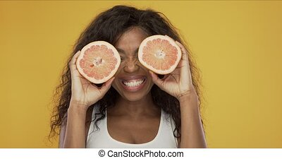 Excited ethnic woman playing with grapefruit - Happy black ...
