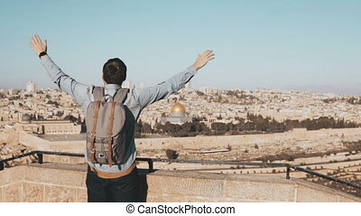 Excited European tourist male raises hands. Israel,...