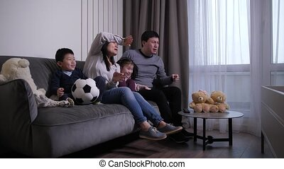 Friendly chinese family with elementary age children actively cheering while watching football game at home. Asian dad, mom and little kids upset with goal scored against their favorite soccer team