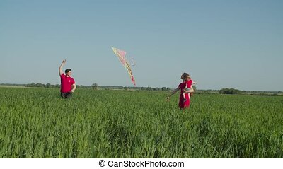 Joyful carefree attractive family with cute toddler daughter running with colorful kite across green wheat field, expressing positivity, happiness, unity and harmony during summer vacations.