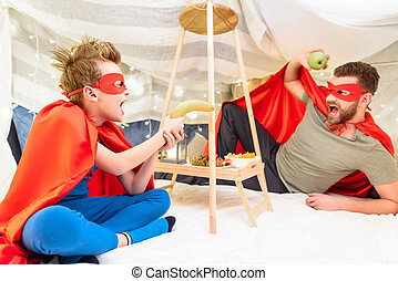 Excited father and son in superhero costumes having fun with fruits in blanket fort