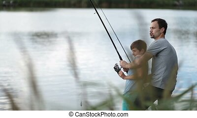 Excited father and son pulling fish out from lake