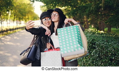 Excited female friends are taking selfie using smartphone and holding shopping bags with purchases on sunny autumn day. Modern technology and youth concept.