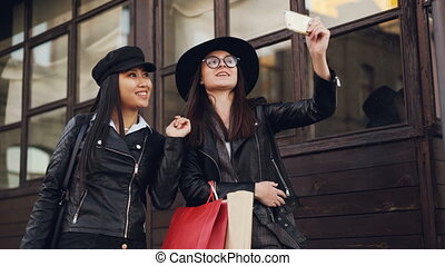 Excited female friends beautiful girls are taking selfie with smartphone and holding paper bags with purchases on autumn day. Modern technology and youth concept.