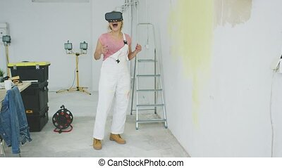 Excited female painter in virtual reality goggles - Happy...