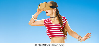 excited fit woman on seashore using VR headset