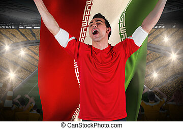 Excited football fan cheering holding iran flag against vast football stadium with fans in yellow