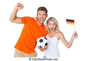 Excited football fan couple cheering at camera