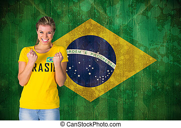 Excited football fan in brasil tshirt against brazil flag in...