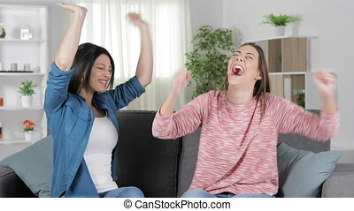 Two excited friends celebrating good news sitting on a couch in the living room at home