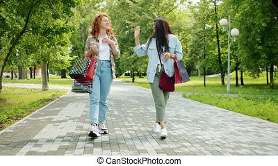Excited friends girls doing high-five during walk in park with colorful shopping bags chatting laughing. Modern lifestyle, shopaholism and friendship concept.