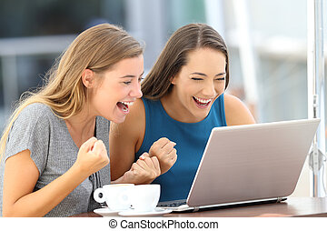 Excited friends finding on line content in a laptop